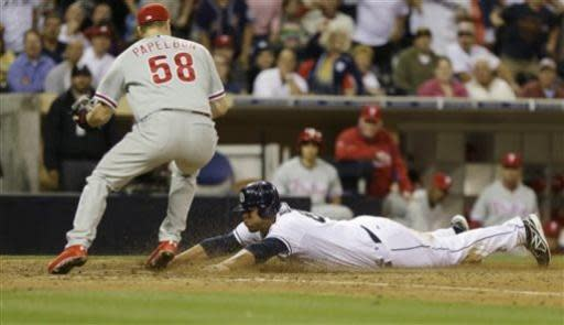 San Diego Padres' Kyle Blanks is safe at home while scoring on a wild pitch as Philadelphia Phillies relief pitcher Jonathan Papelbon goes for a late tag in the ninth inning of a baseball game in San Diego, Monday, June 24, 2013. The run tied the game as the Padres scored three runs in the ninth. (AP Photo/Lenny Ignelzi)