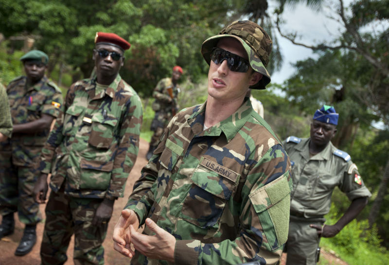"""FILE - In this Sunday, April 29, 2012 file photo, U.S. Army special forces Captain Gregory, 29, from Texas, center, who would only give his first name in accordance with special forces security guidelines, speaks with troops from the Central African Republic and Uganda, in Obo, Central African Republic, where U.S. special forces have paired up with local troops and Ugandan soldiers to seek out Joseph Kony's Lord's Resistance Army (LRA). The U.S.-based Enough Project advocacy group said in a report released Friday, Nov. 9, 2012 that the hunt for the African warlord Joseph Kony is hopeless without more troops and urges American forces to """"play a more operational role"""" on the ground. (AP Photo/Ben Curtis, File)"""