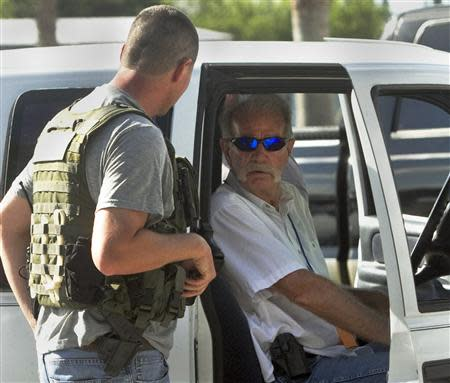 Pastor Terry Jones, (R), talks to a member of the Polk County Sheriff's Department as he sits in his vehicle prior to his arrest after being pulled over while travelling on State Road 37 in Mulberry, Florida September 11, 2013. REUTERS/Michael Wilson/The Lakeland Ledger