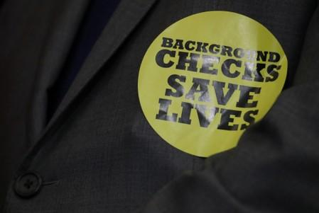 "FILE PHOTO:  A member of Congress wears a ""Background Checks Save Lives"" sticker at news conference to introduce gun control legislation on Capitol Hill in Washington"