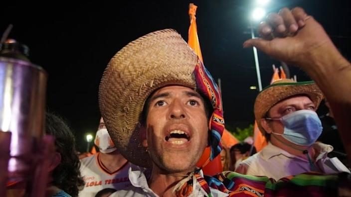 """A supporter of Carlos Mesa, former president and current presidential candidate of the Citizen Community (CC) party, cheers during Mesa""""s closing campaign rally ahead of October 18""""s general elections, in Santa Cruz, Bolivia October 13, 2020"""