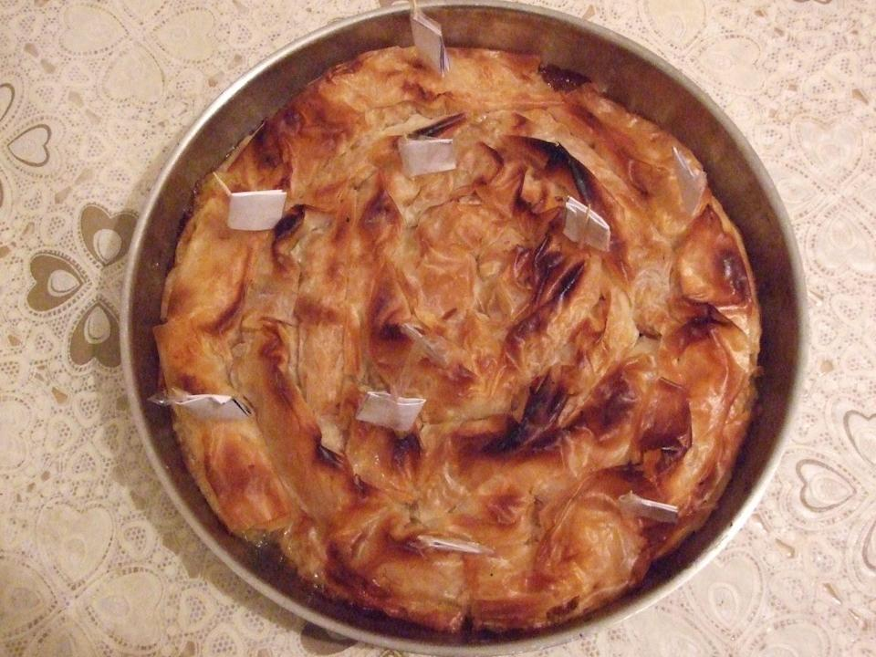 "<p>The Bulgarian banitsa is one of the many round cakes eaten around the world on New Year's Eve. The <a href=""https://bnr.bg/en/post/101207037/time-has-come-to-prepare-the-good-luck-wishes-for-the-traditional-new-years-banitsa"" rel=""nofollow noopener"" target=""_blank"" data-ylk=""slk:shape signifies that the old year has come to and end"" class=""link rapid-noclick-resp"">shape signifies that the old year has come to and end</a>, and the new year gives you a chance to start fresh, according to Bulgaria National Radio. The banitsa is traditionally made with filo pastry, eggs, and fat, but recipes vary in different parts of the country. Regardless of where you go, however, you'll always find twigs or other sticks placed inside the dish, each one representing well wishes for your relatives. </p>"