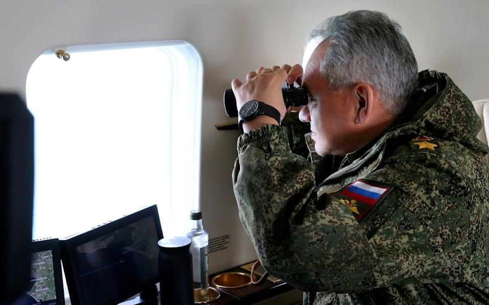 Russian Defense Minister Sergei Shoigu watches drills form a board of military helicopter in Crimea - Vadim Savitsky/Russian Defense Ministry Press Service via AP