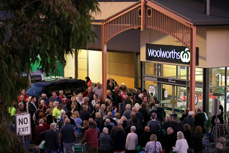 A group of elderly shoppers wait outside a Woolworths to get essential supplies in Sunbury on March 17. Source: Getty