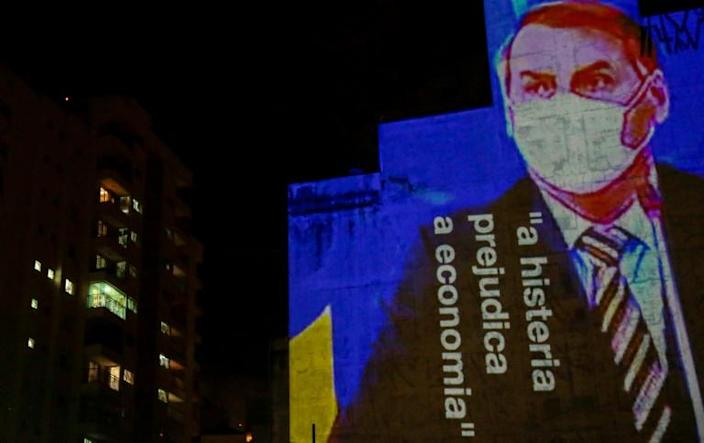 """Image of Brazil's President Bolsonaro with the phrase """"Hysteria Damages the Economy"""" is projected on a building in Sao Paulo to protest his handling of the coronavirus outbreak (AFP Photo/Miguel SCHINCARIOL)"""