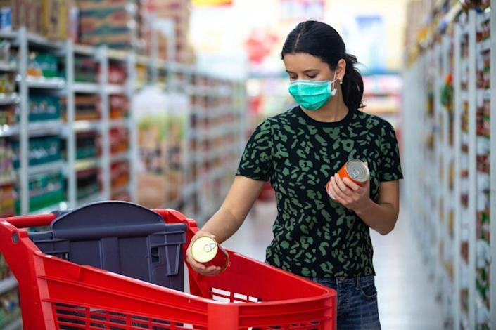 female wears medical mask against coronavirus while grocery shopping in supermarket or store- health, safety and pandemic concept - young woman wearing protective mask and stockpiling food