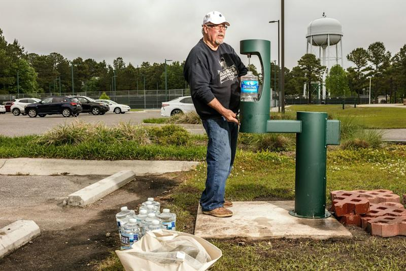 Ken Madsen fills up bottles with noncontaminated water at Ogden Park in Wilmington. Like many residents, Madsen will not drink water from his faucet since the discovery of GenX in the supply.