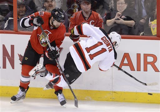 Ottawa Senators left wing Guillaume Latendresse, left, collides with New Jersey Devils right wing Stephen Gionta during first period NHL action in Ottawa, on Monday March 25, 2013. (AP Photo/The Canadian Press, Adrian Wyld)