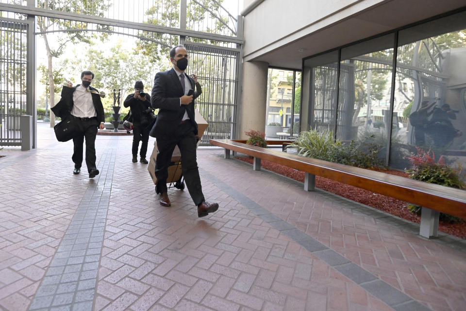 Defense attorneys for Elizabeth Holmes, founder and CEO of Theranos, arrives at the federal courthouse for jury selection in her trial, Tuesday, Aug. 31, 2021, in San Jose, Calif. Holmes faces 12 felony counts alleging she engineered a massive fraud that duped a litany of rich investors with a blood-testing technology that she promised would be able to screen for hundreds of diseases with a finger prick. (AP Photo/Nic Coury)