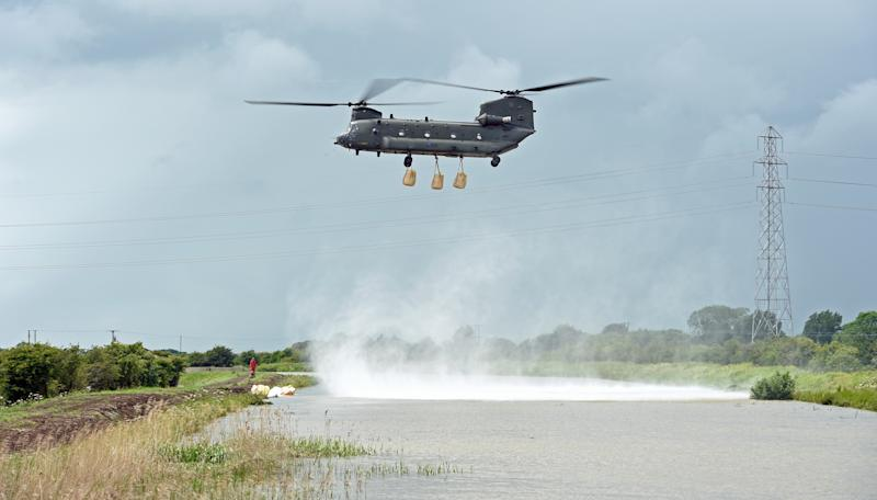 An RAF Chinook helicopter delivers sandbags to plug a gap where the River Steeping burst its banks.