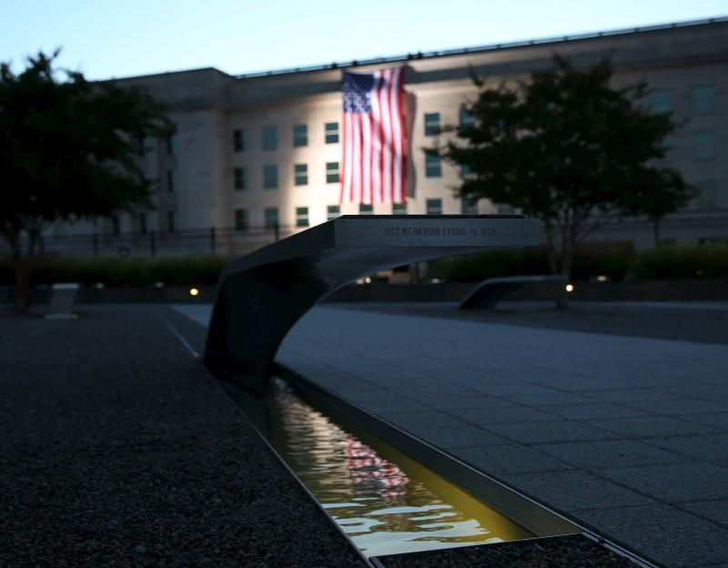 A United States flag is reflected at 9/11 Memorial after being at sunrise at the Pentagon on fourteenth anniversary of 9/11 attacks