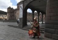 A man dressed as Inca ruler Manco Capac, who according to some historians was the first governor and founder of the Inca civilization in Cusco waits for tourists on an empty street in modern-day Cusco, Peru, Monday, Oct. 26, 2020. All major sites around the Cusco are currently open for free, in hopes of sparking any tourism after the COVID-19 pandemic brought it to a standstill, leaving reenactors like this man interpreting Manco Capac facing severe unemployment. (AP Photo/Martin Mejia)