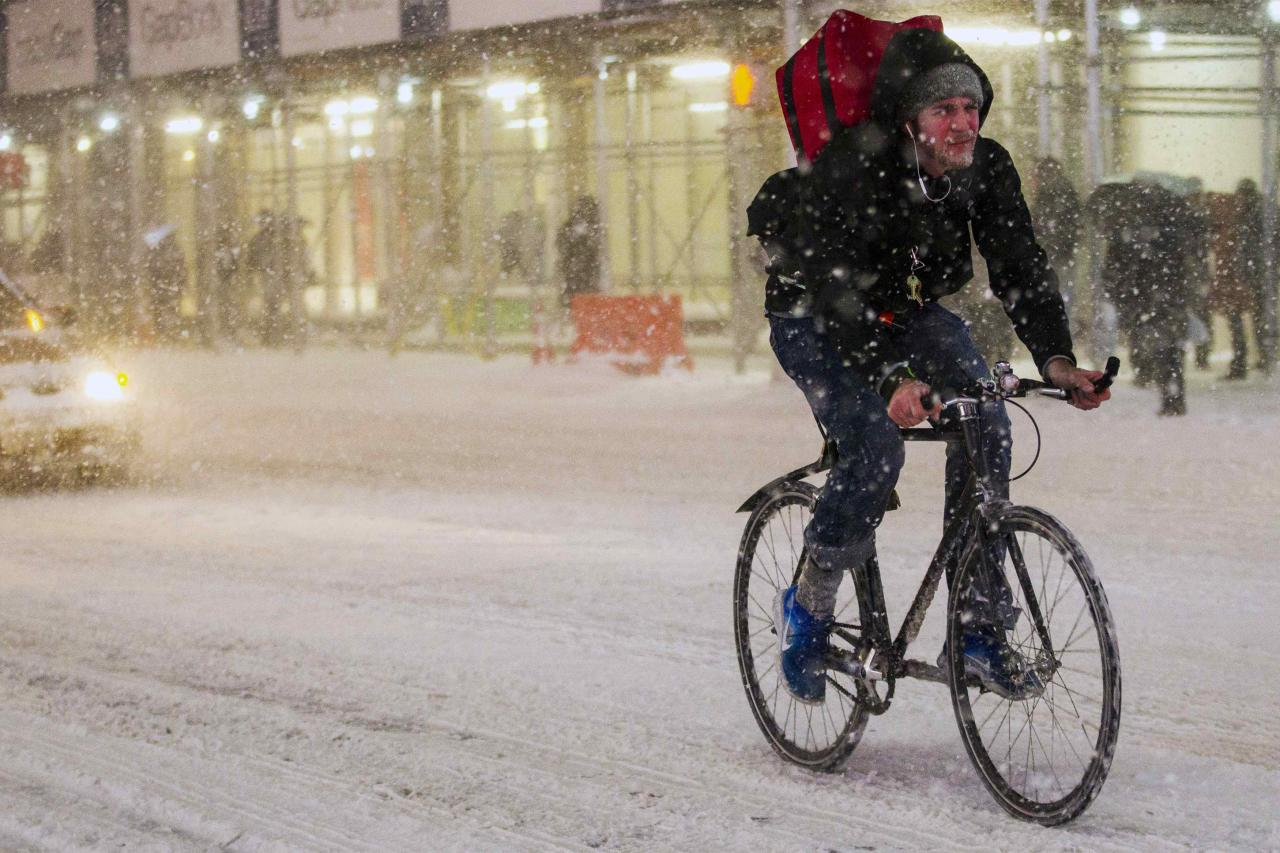 A man rides his bike in the snow storm through Times Square in Manhattan in New York January 21, 2014. A winter storm packing snow and Arctic cold slammed the northeastern United States on Tuesday, grounding 3,000 flights, shutting down governments and schools and making travel a potential nightmare for millions.REUTERS/Brendan McDermid (UNITED STATES - Tags: ENVIRONMENT)