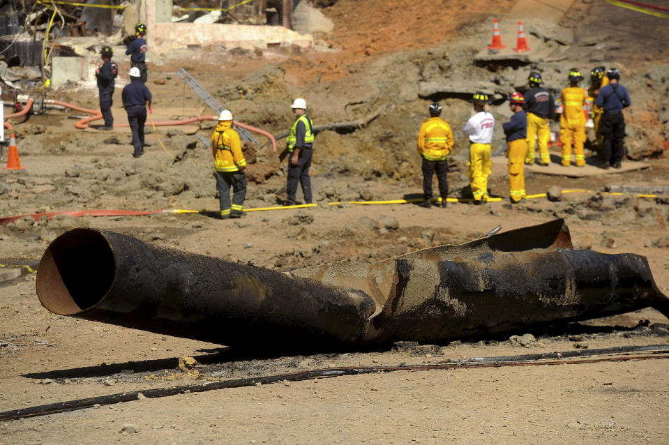 FILE - In this Sept. 11, 2010, file photo, a Pacific Gas & Electric natural gas line lies broken on a San Bruno, Calif., road after a massive explosion. U.S. prosecutors are urging a federal judge to work with a court-appointed monitor to determine ways Pacific Gas & Electric Co. can prevent its equipment from starting more wildfires. District Judge William Alsup overseeing Pacific Gas & Electric's criminal probation is holding a hearing Tuesday, May 4, 2021, to consider whether Pacific Gas & Electric violated its criminal probation from a fatal 2010 natural gas explosion by sparking the October 2019 Kincade Fire north of San Francisco.(AP Photo/Noah Berger, File)