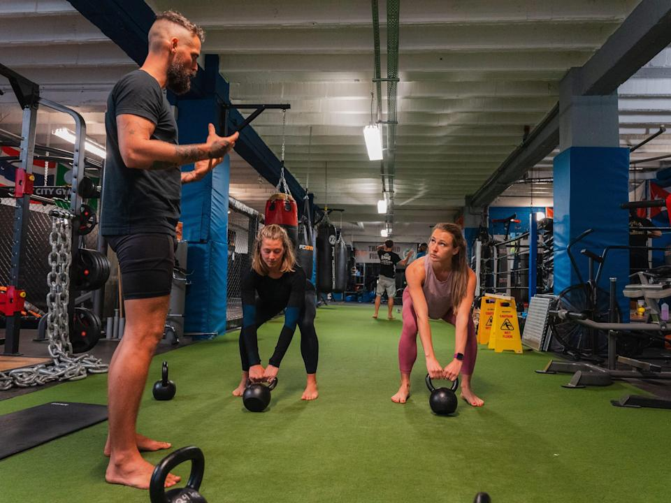 Rachel learning to kettlebell swing with Jay and Steph Rose.