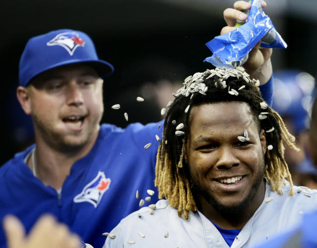 Toronto Blue Jays' Vladimir Guerrero Jr. gets sunflowers seeds dumped on his head by Justin Smoak, left, after hitting a grand slam against the Detroit Tigers during the fifth inning of a baseball game, Saturday, July 20, 2019, in Detroit. (AP Photo/Duane Burleson)