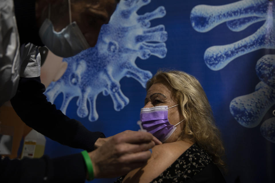 A woman receives a coronavirus vaccine from medical staff at a COVID-19 vaccination center in Ramat Gan, Israel, Sunday, Jan. 3, 2021. (AP Photo/Oded Balilty)