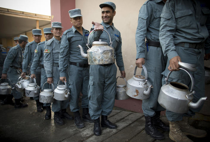 FILE - In this Oct. 9, 2012 file photo, Afghan National Police officers line up with teapots to get their breakfast at the Police Academy in Kabul, Afghanistan. The 350,000-strong Afghan National Security Forces, made up mostly of the army and police, took heavy losses after assuming responsibility for security around the country from the U.S.-led international coalition in June. They took the lead against an insurgency that had promised to retake lost territory as foreign forces began a gradual withdrawal that will see them all home by the end of 2014. (AP Photo/Anja Niedringhaus, File)