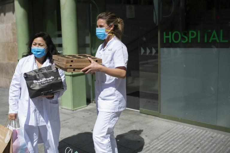 Two healthcare workers receive sushi and pizzas delivered by Delivery4Heroes to Barcelona's Hospital Clinic