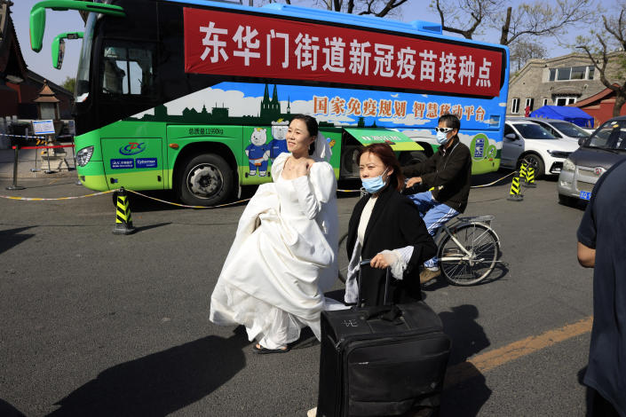 A woman in a wedding gown passes a bus offering free coronavirus vaccinations outside the Forbidden City in Beijing on Wednesday, April 14, 2021. China's success at controlling COVID-19 has resulted in a population that has seemed almost reluctant to get vaccinated. Now it is accelerating its inoculation campaign by offering incentives — free eggs, store coupons and discounts on groceries and merchandise — to those getting a shot. (AP Photo/Ng Han Guan)