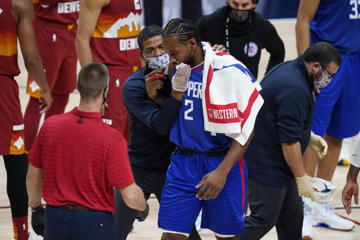 Los Angeles Clippers forward Kawhi Leonard is helped off the court after suffering an injury during the second half of the team's NBA basketball game against the Denver Nuggets on Friday, Dec. 25, 2020, in Denver. (AP Photo/David Zalubowski)