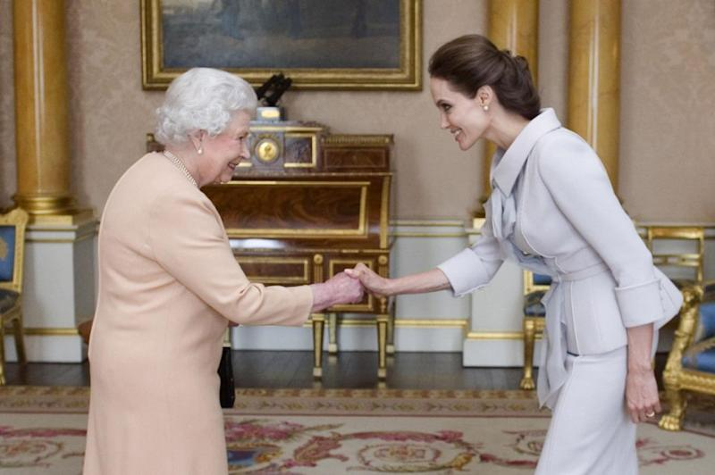 Angelina Jolie is presented with the Insignia of an Honorary Dame Grand Cross of the Most Distinguished Order of St Michael and St George by Britain's Queen Elizabeth on October 10, 2014. Source: Getty.