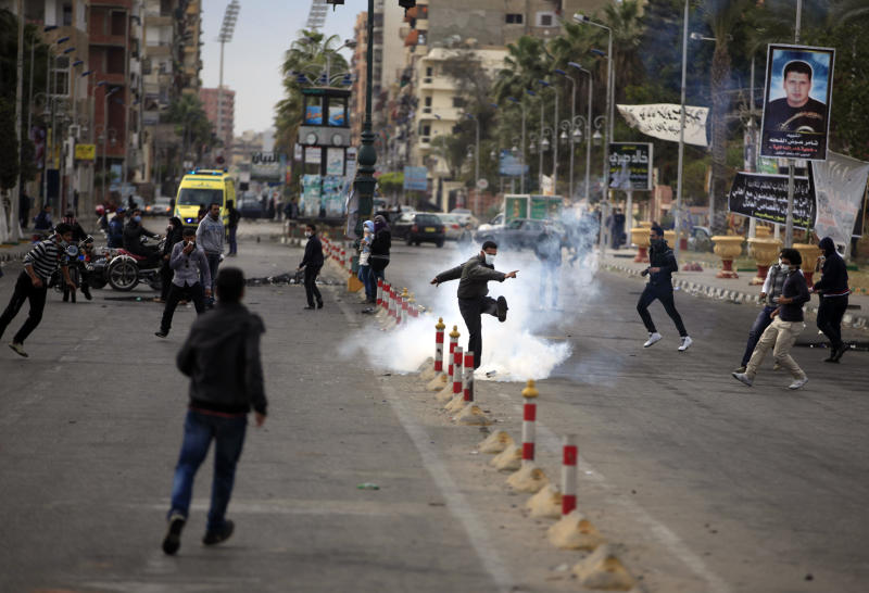 An Egyptian protester kicks a tear gas canister fired by riot police, not pictured, during clashes near a state security building in Port Said, Egypt, Thursday, March 7, 2013. Clashes between protesters and police continued into a fifth day on Thursday in the restive Egyptian city of Port Said. (AP Photo/Khalil Hamra)