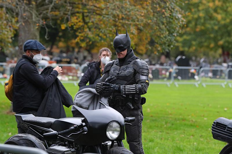 A man dressed as Batman gets on a motorbike during the filming of The Batman taking place in Liverpool.