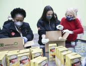 From left, U.S. Representatives Sheila Jackson Lee, Alexandria Ocasio-Cortez, and Sylvia Garcia, fill boxes at the Houston Food Bank on Saturday, Feb. 20, 2021. President Joe Biden declared a major disaster in Texas on Friday, directing federal agencies to help in the recovery. (Elizabeth Conley/Houston Chronicle via AP)