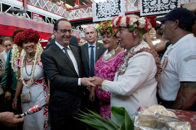 French President Francois Hollande (L) meets inhabitants as he visits the market in Papeete, the capital of the French Polynesian island of Tahiti on February 22, 2016, during a two-day visit (AFP Photo/Gregory Boissy)