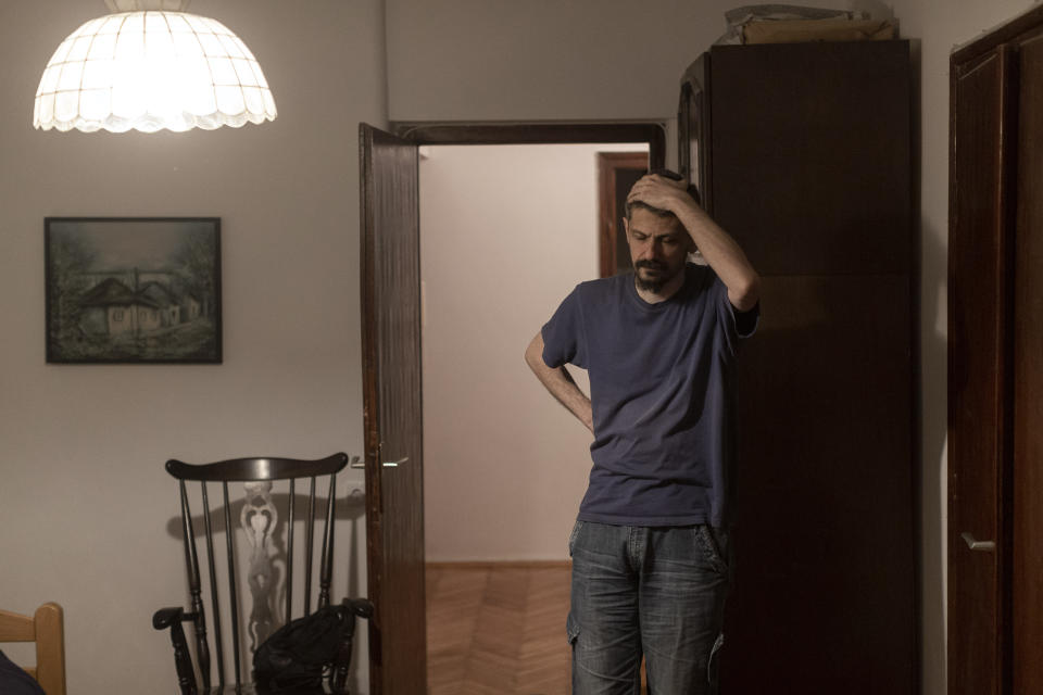 In this photo taken on Friday, July 2, 2021, Nemanja Dragic, 36, stands inside his living room, as noise from a local bar permeates his apartment in Belgrade, Serbia. Serbia's capital is vibrating with nightlife again after over a year of pandemic restrictions. Cafes, bars and fun-hungry customers are celebrating a summer boom in business and entertainment options. But the accompanying loud music and noise are a bust for residents across Belgrade. (AP Photo/Marko Drobnjakovic)