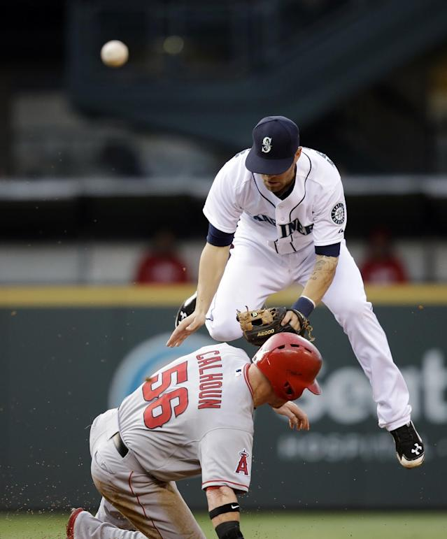 Seattle Mariners second baseman Nick Franklin, right, tries to get out of the way as Los Angeles Angels' Kole Calhoun slides into second base during the third inning of a baseball game Thursday, May 29, 2014, in Seattle. Calhoun was out, but Erick Aybar was safe at first. (AP Photo/Elaine Thompson)