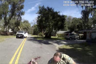 """In this Feb. 23, 2020 image taken from Glynn, Ga., County Police body camera video, an officer applies pressure to Ahmaud Arbery's gunshot wound outside the port city of Brunswick, Ga. Father and son Gregory and Travis McMichael were arrested on murder charges in May, more than two months after Arbery, a 25-year-old Black man, was fatally shot while running in their neighborhood. A third man, William """"Roddie"""" Bryan Jr., who shot cellphone video of the incident was charged with murder for joining the chase. (Glynn County Police via AP)"""