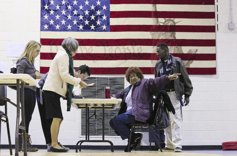 Poll worker, Dollie Scott, center, points the way for voters who cast their ballots on Tuesday, March 6, 2012, at E. Rivers Elementary School, in Atlanta. Republican Presidential candidate Former House Speaker Newt Gingrich was favored to win in Georgia on Tuesday, but his rivals have spent time and resources in the state, hoping to grab a share of the state's 76 delegates.(AP Photo/Atlanta Journal & Constitution, John Spink) MARIETTA DAILY OUT; GWINNETT DAILY POST OUT