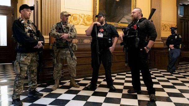 PHOTO: Members of a militia group stand near the doors to the chamber in the capitol building in Lansing, Mich., April 30, 2020. (Seth Herald/Reuters, FILE)