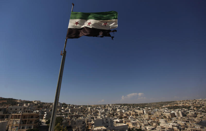 FILE - In this Tuesday, June 12, 2012 file photo, a Syrian revolutionary flag waves on top of a building on the outskirts of Aleppo, Syria. During two weeks with rebels in northern Syria, three Associated Press journalists found more than 20 rebel groups who often destroy government army posts and convoys but lack the weapons and unity to do more than gradually chip away at the regime of President Bashar Assad _ a recipe for a long, bloody insurgency.(AP Photo/Khalil Hamra, File)
