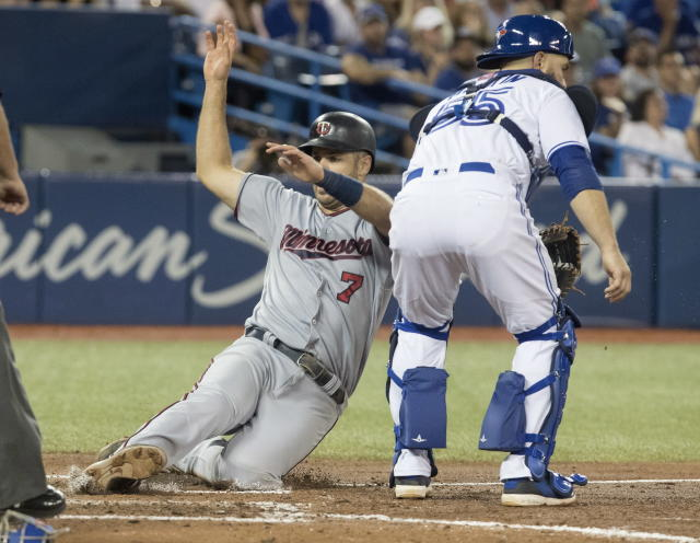 Minnesota Twins' Joe Mauer scores as Toronto Blue Jays' catcher Martin Russell waits for the late throw to the plate in the sixth inning of their baseball game in Toronto on Tuesday, July 24, 2018. (Fred Thornhill/The Canadian Press via AP)