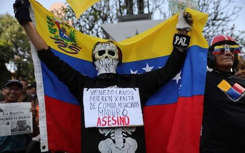 """<span>An anti-government protester wears signs asking for humanitarian aid and a message on his chest that reads in Spanish: """"Venezuelans die for lack of medicines. Maduro is an assassin""""</span>"""
