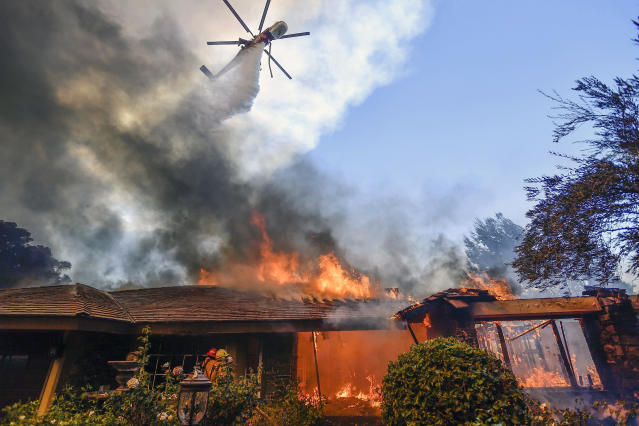 <p>A helicopter dumps water on a home as firefighters battle a wildfire in Anaheim Hills in Anaheim, Calif., Monday, Oct. 9, 2017. Wildfires whipped by powerful winds swept through Northern California sending residents on a headlong flight to safety through smoke and flames as homes burned. (Photo: Jeff Gritchen/The Orange County Register via AP) </p>