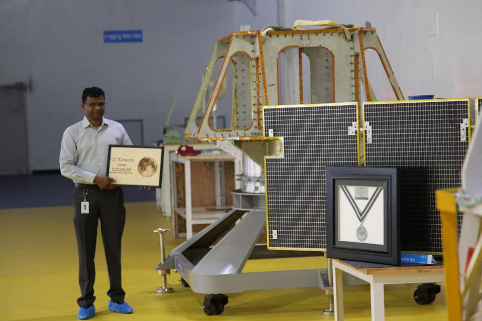 man holding plaque beside a model of a robotic spacecraft