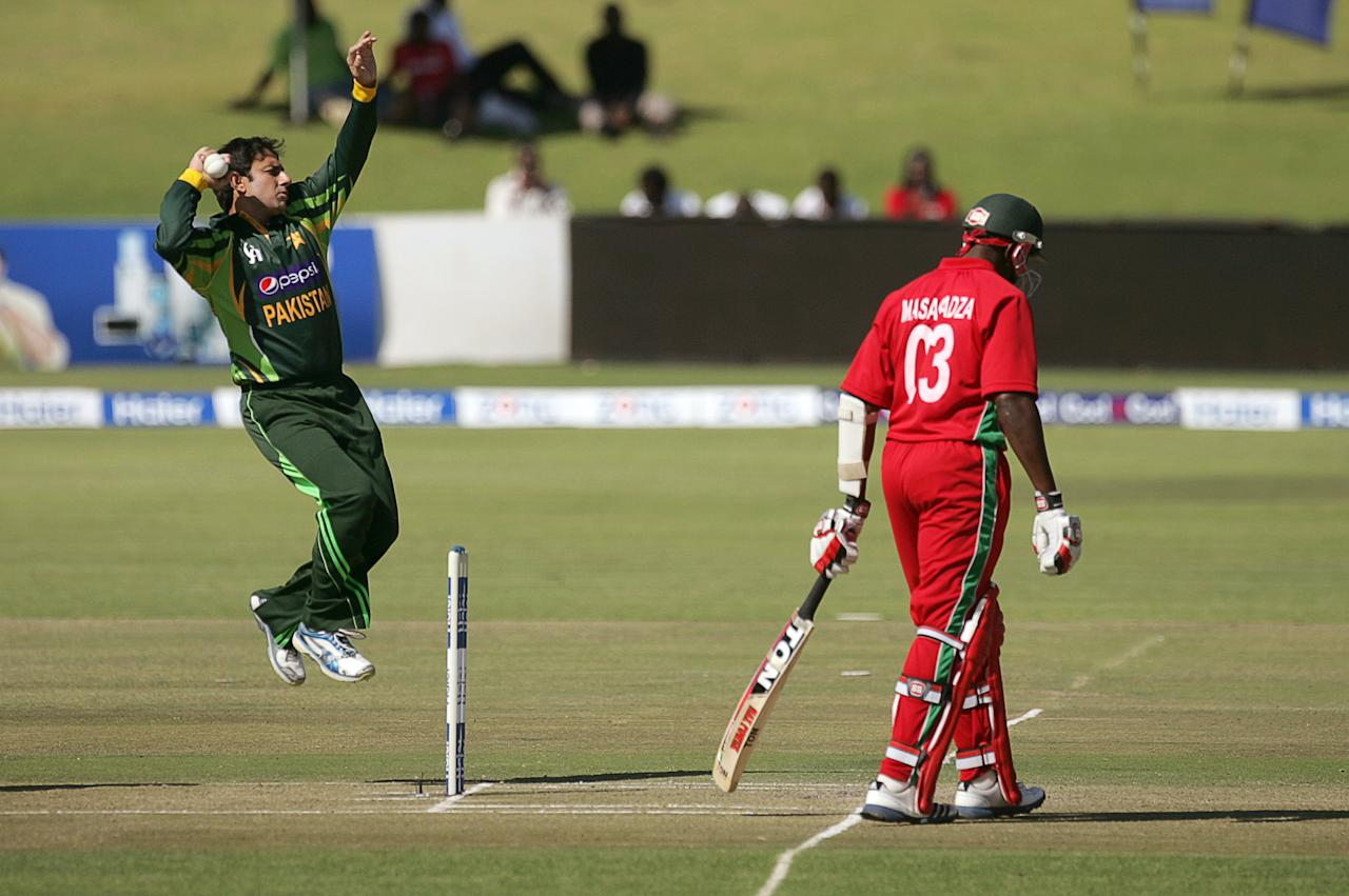 Pakistan's bowler Saeed Ajmal (L) in action as Zimbabwe batsman Hamilton Masakdza looks on during the first game of the three match ODI cricket series between Pakistan and hosts Zimbabwe at the Harare Sports Club August 27, 2013. AFP PHOTO / JEKESAI NJIKIZANA        (Photo credit should read JEKESAI NJIKIZANA/AFP/Getty Images)