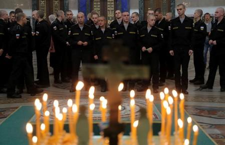 Russian servicemen attend a memorial service for sailors killed in a Russian submarine, which caught fire in the area of the Barents Sea, at the Naval Cathedral of Saint Nicholas in Kronstadt
