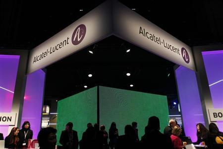 Visitors walk at the Alcatel-Lucent booth at the Mobile World Congress in Barcelona