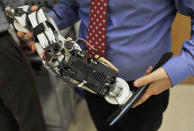 """In this Oct. 25, 2012 photo, Dr. Levi Hargrove, lead researcher for the Rehabilitation Institute of Chicago's Center for Bionic Medicine, holds an experimental """"bionic"""" prosthetic leg at the institute. Zac Vawter, a 31-year-old software engineer who lost his right leg in a motorcycle accident, will help test the trailblazing prosthetic leg, that's controlled by his thoughts, when he attempts to climb 103 flights of stairs to the top of Chicago's Willis Tower on Sunday, Nov. 4. (AP Photo/Brian Kersey)"""