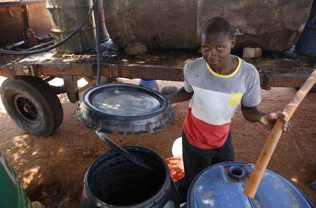 A man draws water from a communal tap in Disaneng village outside Mafikeng