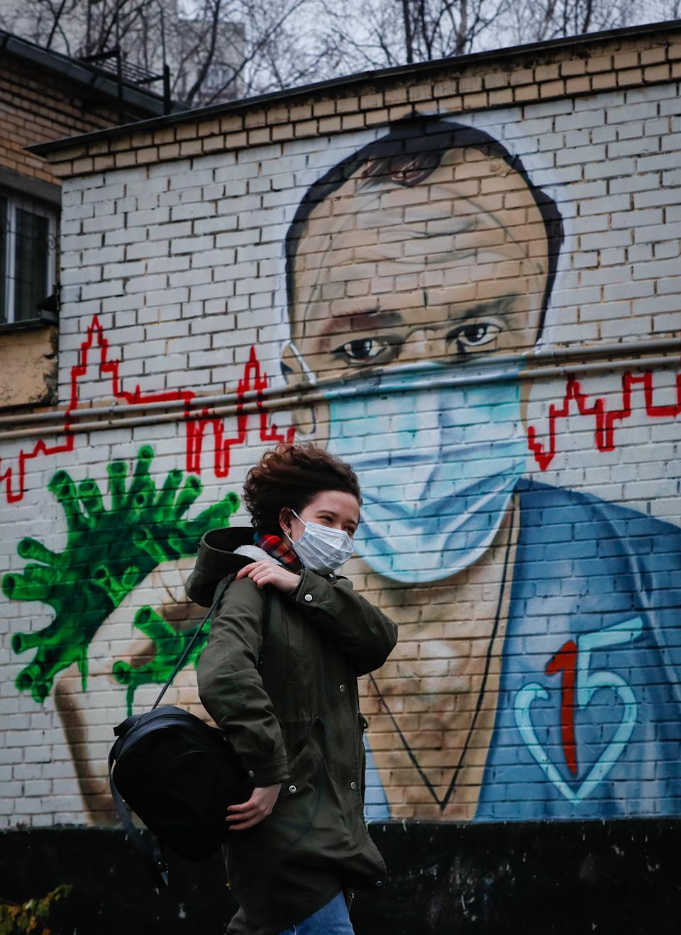 A woman walks past a mural of a doctor fighting coronavirus in Russia.