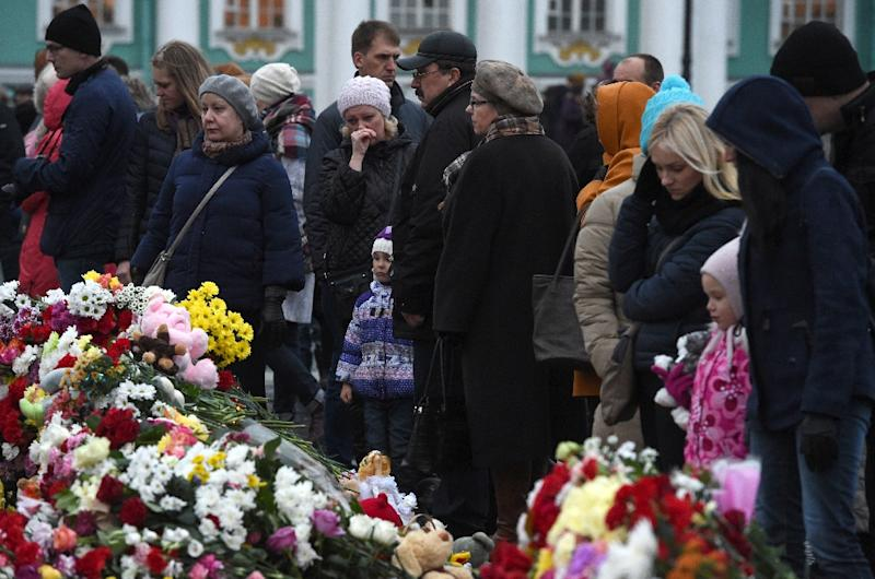 People stand next to flowers at a makeshift memorial for the victims of the Russian MetroJet Airbus A321 crash on November 4, 2015 in Saint Petersburg (AFP Photo/Vasily Maximov)