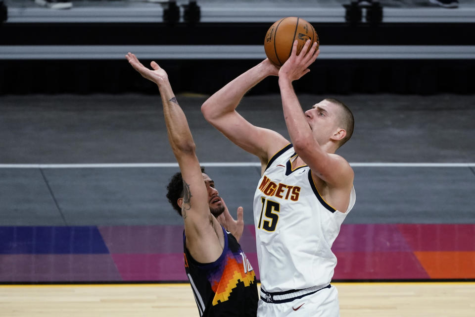 Denver Nuggets center Nikola Jokic (15) shoots over Phoenix Suns forward Abdel Nader during the first half of an NBA basketball game Saturday, Jan. 23, 2021, in Phoenix. (AP Photo/Rick Scuteri)