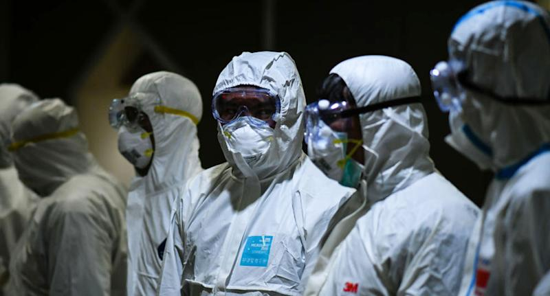 Six medical workers in full protective gear fighting coronavirus.