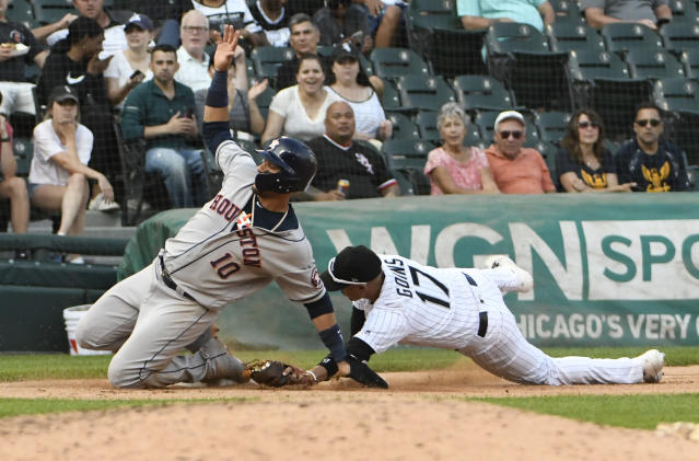 Houston Astros' Yuli Gurriel (10) slides safely into third base as Chicago White Sox third baseman Ryan Goins (17) makes a late tag during the eighth inning of game one of a baseball doubleheader, Tuesday, Aug. 13, 2019, in Chicago. (AP Photo/David Banks)